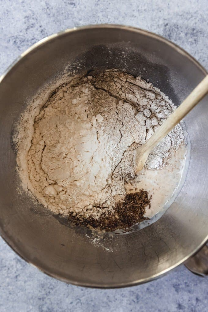 An image of yeast, wheat flour, rye flour, and caraway seeds in a bowl to make homemade rye bread dough.
