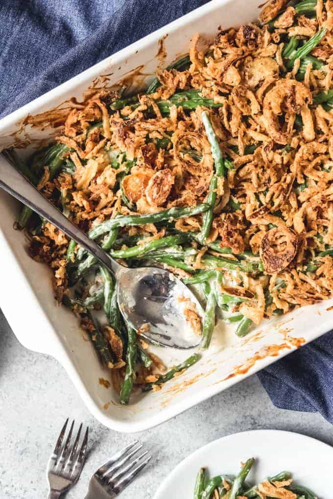 a close up of a white baking dish with green bean casserole and a serving spoon inside