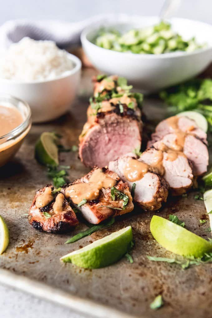 This Grilled Thai Pork Tenderloin with Coconut Lime Peanut Sauce is packed with delicious flavors and is perfect served with coconut jasmine rice and an easy cucumber salad for dinner.  Don't forget coconut mango sticky rice for dessert!