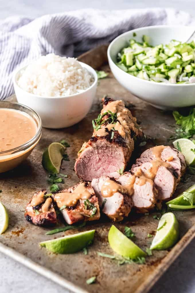 Grilled Thai Pork Tenderloin on a tray with a bowl of rice and other ingredients to the side