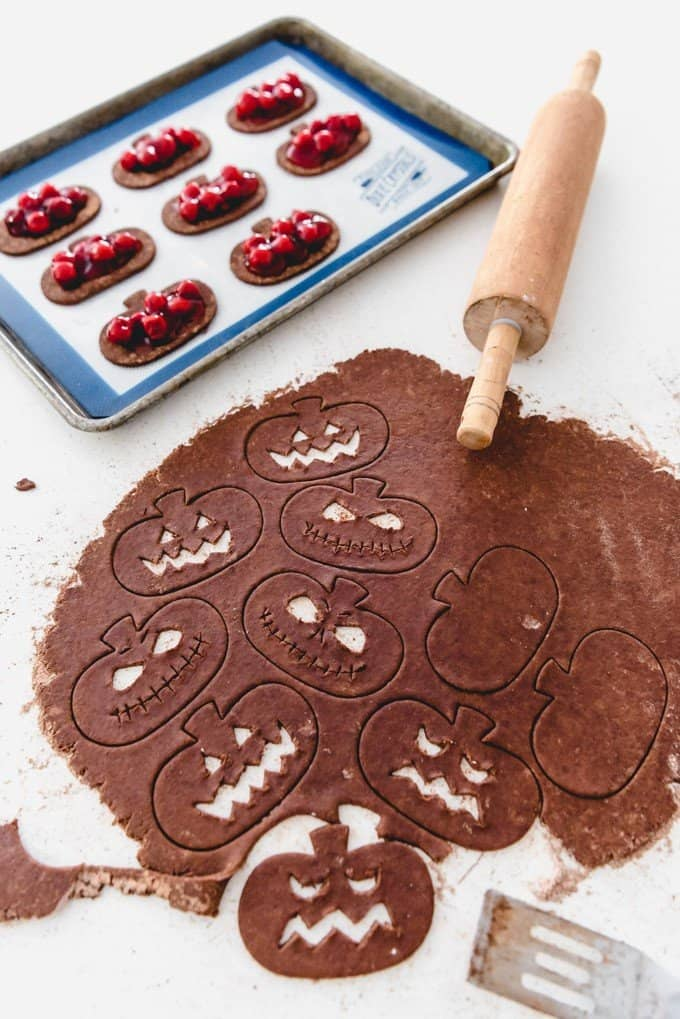 An image of chocolate pie crust dough rolled out and cut into jack-o-lantern shapes.