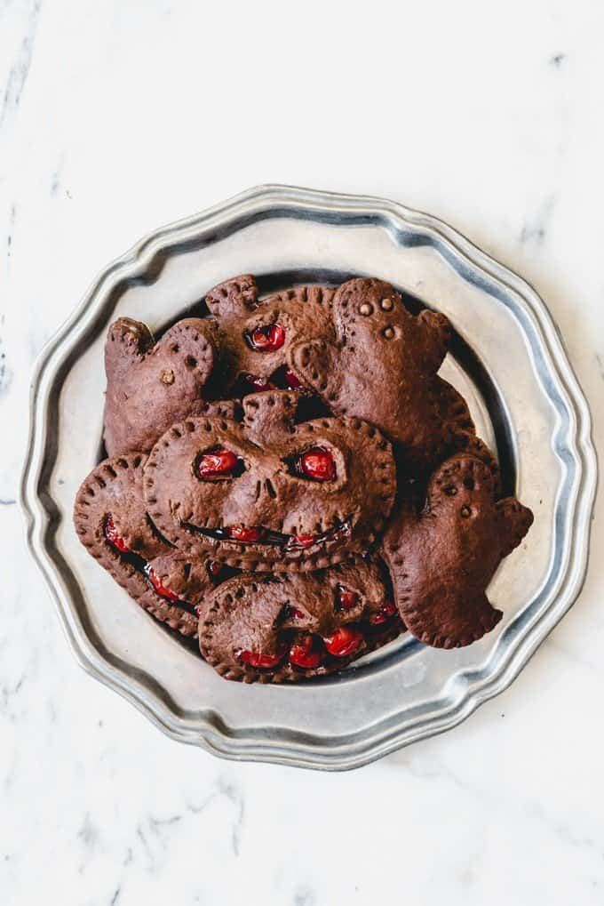 An image of chocolate cherry hand pies cut out in pumpkin shapes with Jack-o-Lantern faces.