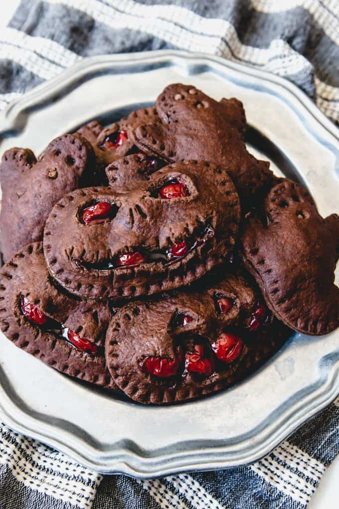 An image of a plate of cherry chocolate hand pies in the shape of jack-o-lanterns for Halloween.