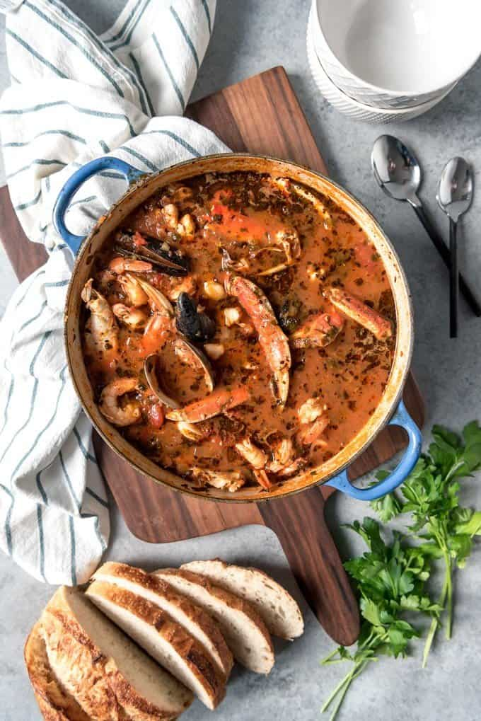 A large pot of classic, authentic cioppino seafood stew with a loaf of sliced sourdough bread next to it.