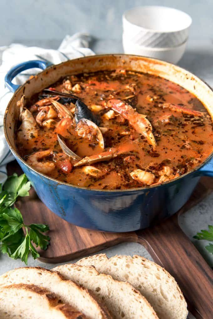 An image of a large dutch oven pot of San Francisco cioppino seafood stew made with the freshest seafood available and served with plenty of sliced sourdough bread.
