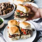 These Slow Cooker Asian Pulled Pork Sliders are easy and delicious weeknight fare that's just as perfect for a game day tailgating party.  Pile the tender, juicy pork on soft buns with plenty of crunchy coleslaw and enjoy!