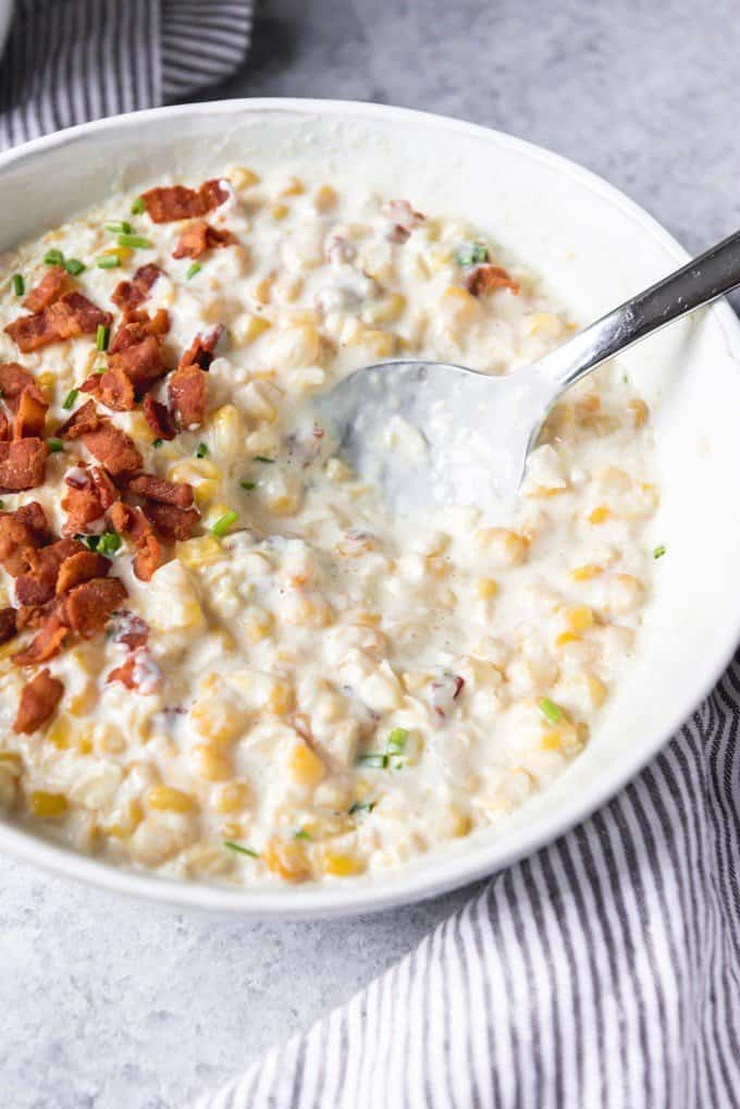 a white bowl filled with creamed corn and a spoon