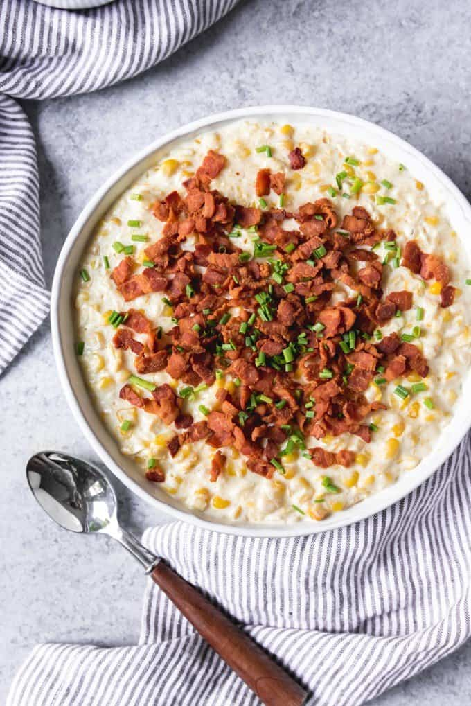 An image of a large serving bowl of slow cooker creamed corn with bacon and chives sprinkled over the top.
