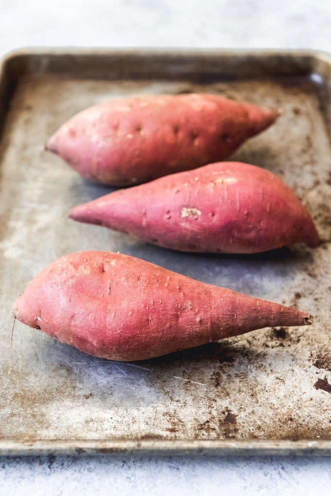 An image of sweet potatoes in their skins on a pan for roasting in the oven.