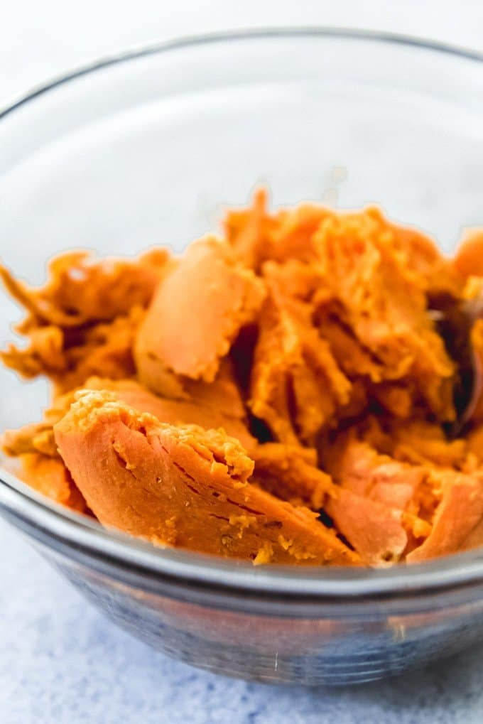 An image of baked sweet potatoes that have been scooped out of their skins and into a bowl for mashing.