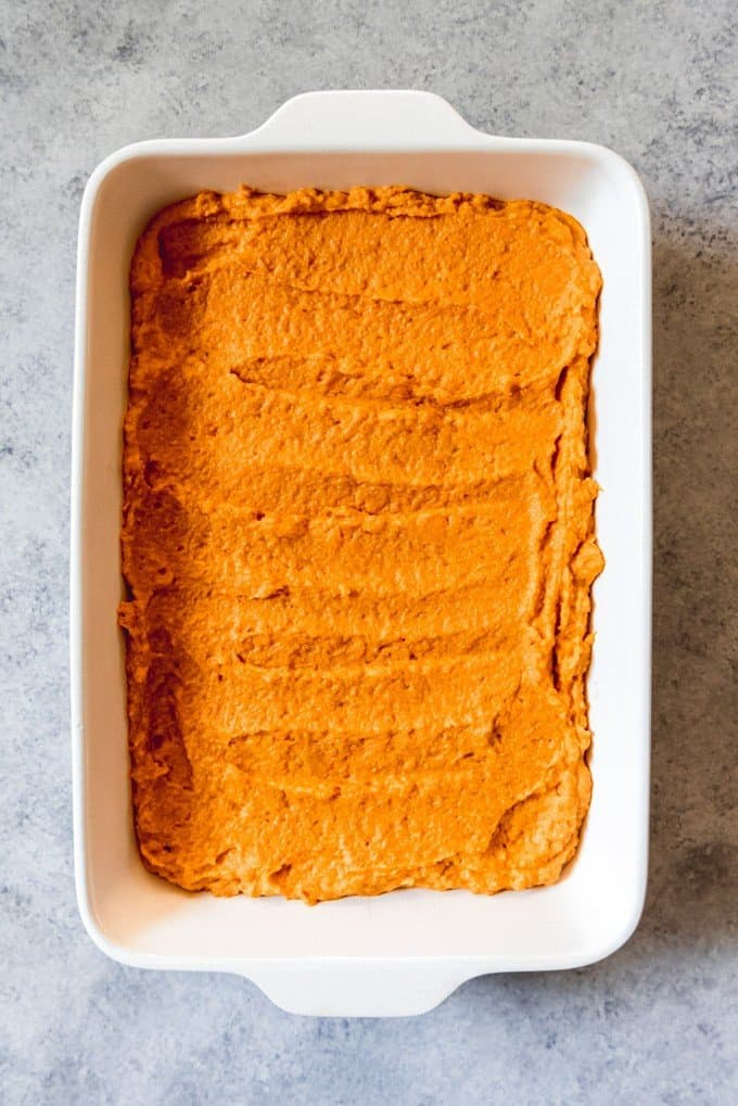 An image of mashed sweet potatoes with brown sugar, milk, butter, and cinnamon in a serving dish, ready to be topped with marshmallows for sweet potato casserole.