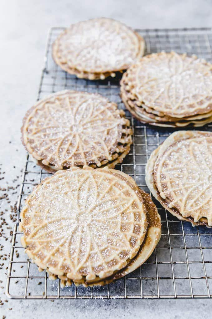 powdered sugar dusted pizzelles on a wire rack