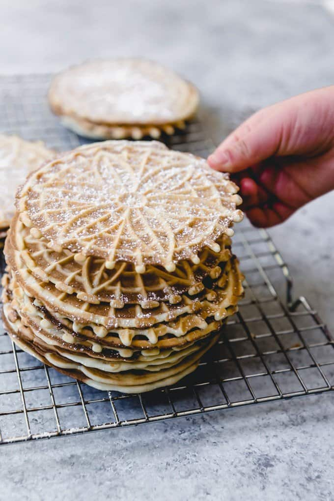 An image of a hand lifting a classic Italian pizzelle dusted with powdered sugar from off a stack of pizzelles.