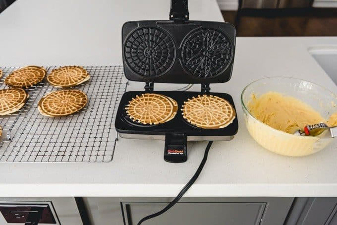 An image of a pizzelle maker on a counter with anise pizzelle batter and cooked pizzelles on top and beside the iron.