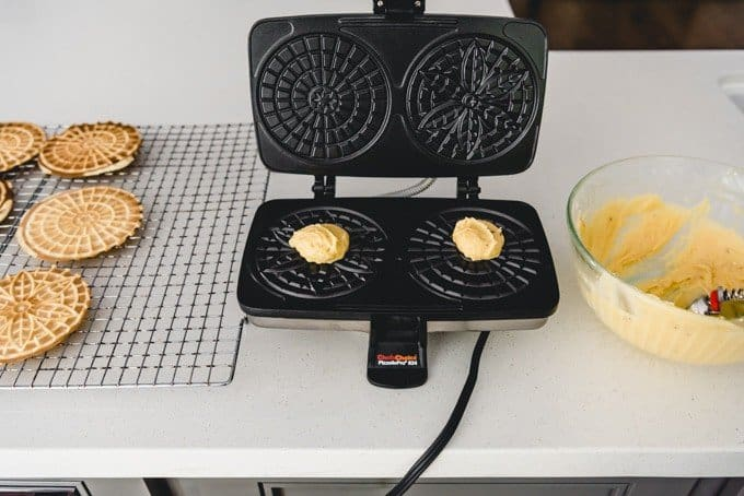 An image of a hot pizzelle iron with anise pizzelle batter on it ready to be pressed into cookie form.