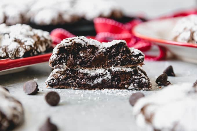 An image of a soft chocolate crinkle cookie with melted chocolate chips inside it and a crackly powdered sugar coating on the exterior.