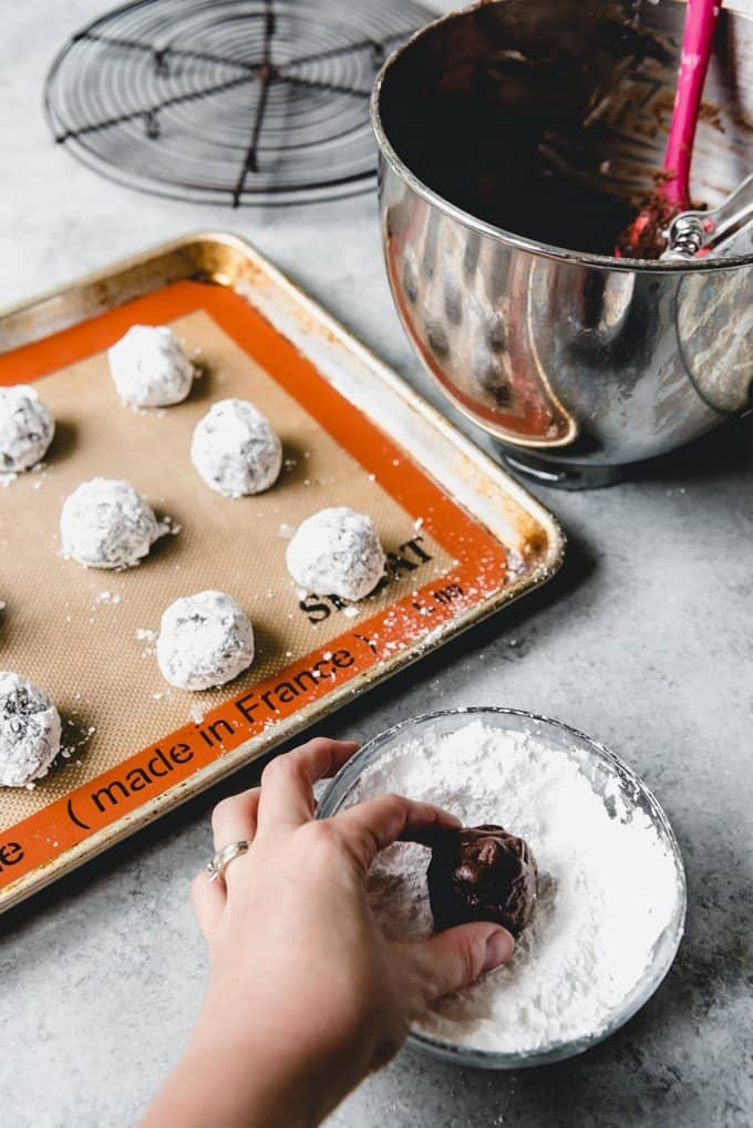 An image of a hand rolling a ball of chocolate crinkle cookie dough in powdered sugar.