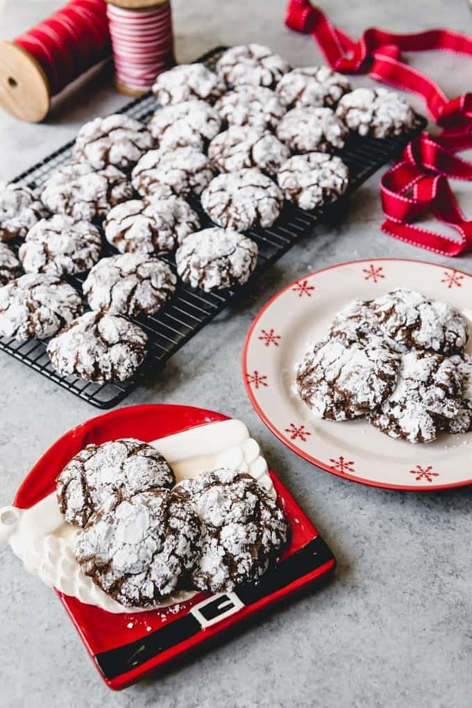 An image of double chocolate crinkle cookies arranged on a Santa Christmas plate with more cookies cooling on a wire rack behind them.