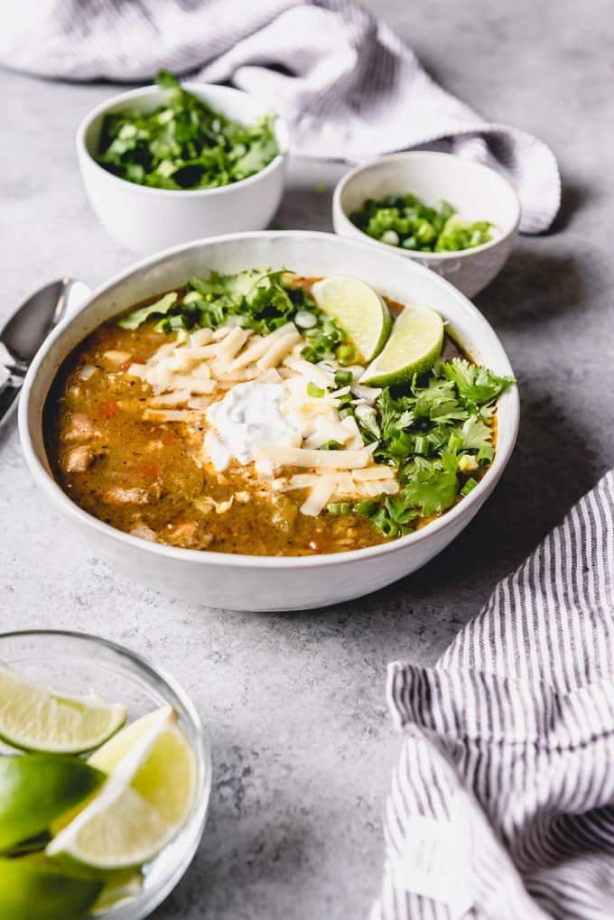 An image of a bowl of slow cooker pork chili verde topped with lime wedges, fresh cilantro, green onions, cheese and sour cream.