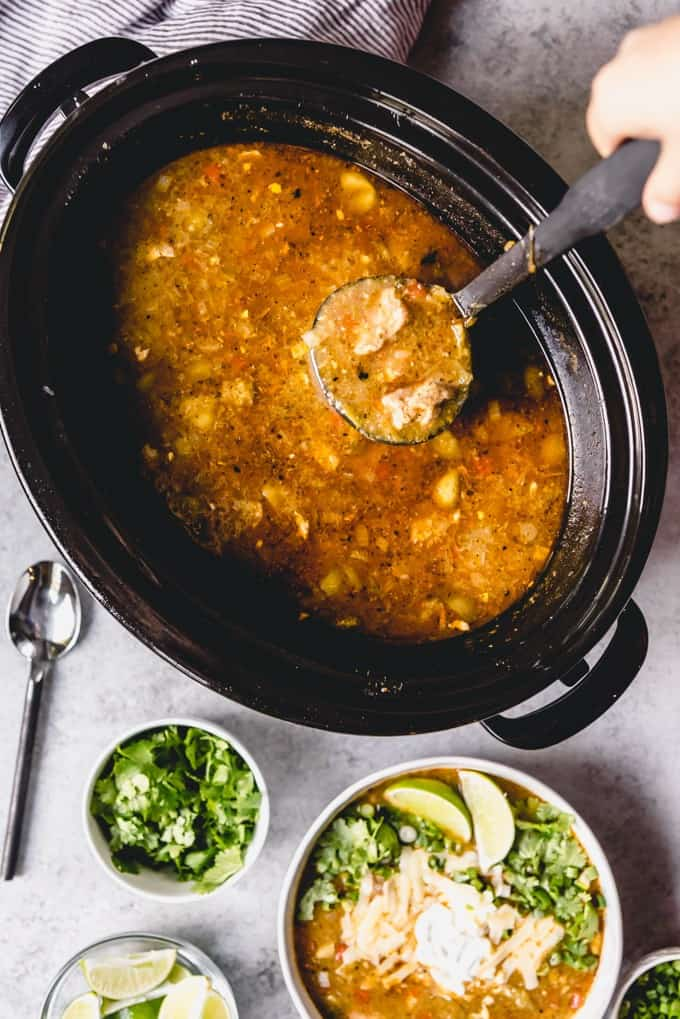 An image of a hand lifting a ladle full of pork chili verde out of a crock pot, next to a bowl of pork chili verde topped with all the fixins.