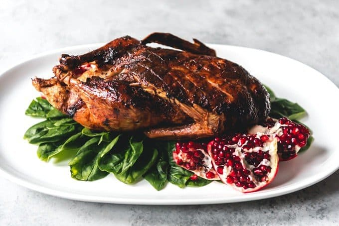 An image of a whole roasted duck on a serving platter for an alternative Thanksgiving dinner.