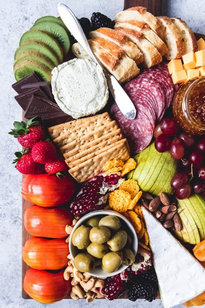 An image of an epic cheese board with seasonal winter fruits, salami, and crackers, perfect for holiday entertaining.