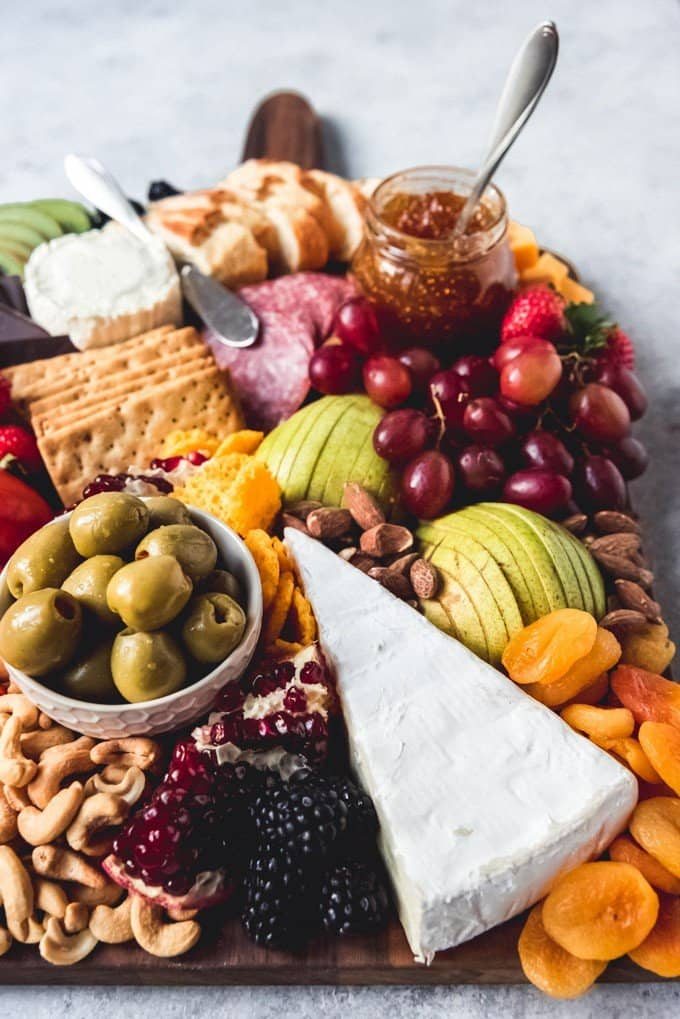 fresh fruit and nuts on a platter with cheeses and more