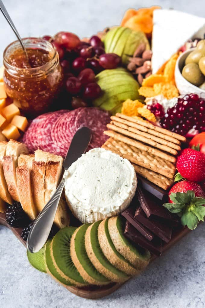 An image of an almost overflowing fruit and cheese platter with crusty bread, crackers, jams, and chocolate for extra variety!