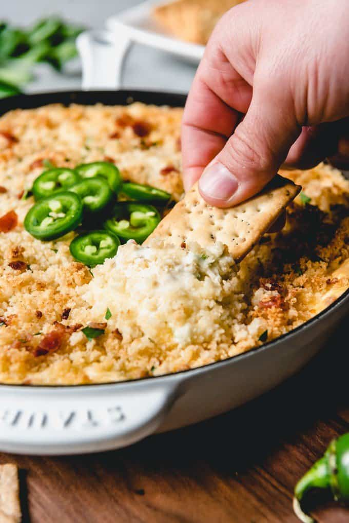 An image of a hand holding a cracker scooping bacon jalapeno popper dip.