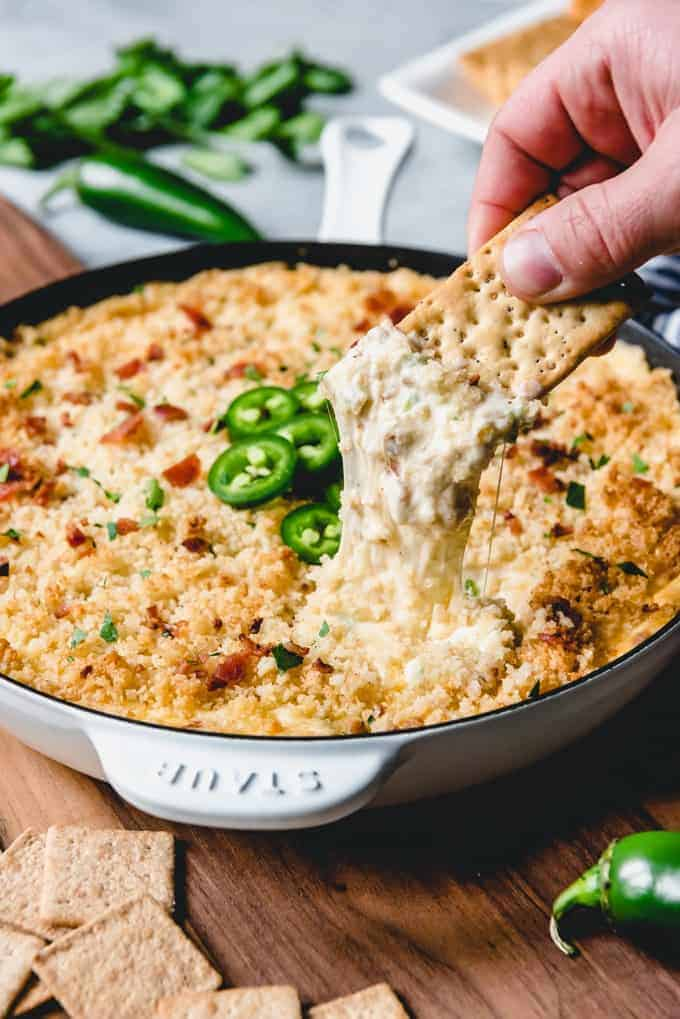 a cracker pulling some cheesy jalapeno dip out of a skillet