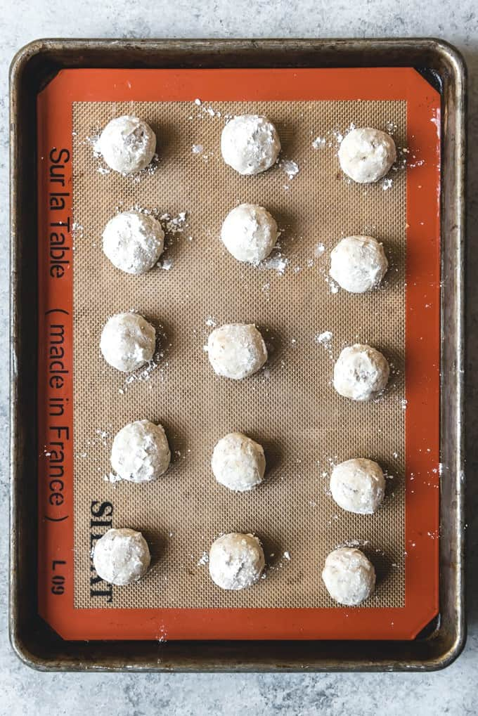 An image of Russian Tea Cakes rolled in powdered sugar on a baking sheet.