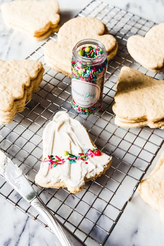 An image of a frosted sugar cookie with the best sugar cookie frosting recipe, decorated with colorful sprinkles.