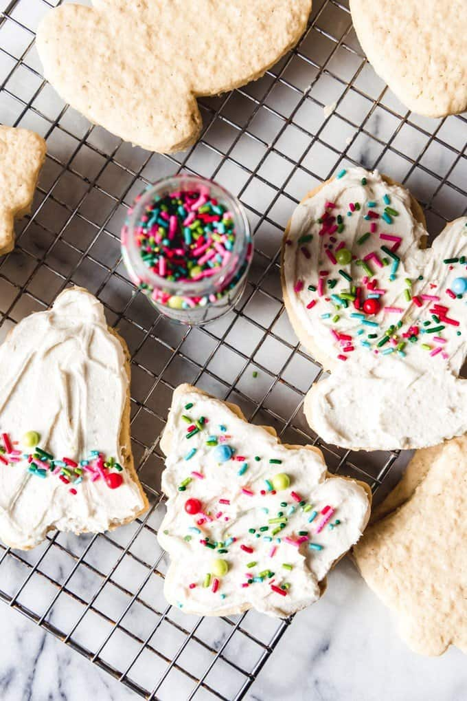 An image of old-fashioned Christmas cookies made with rolled oats and rolled and cut into Christmas shapes, then frosted with buttercream frosting and decorated with sprinkles.