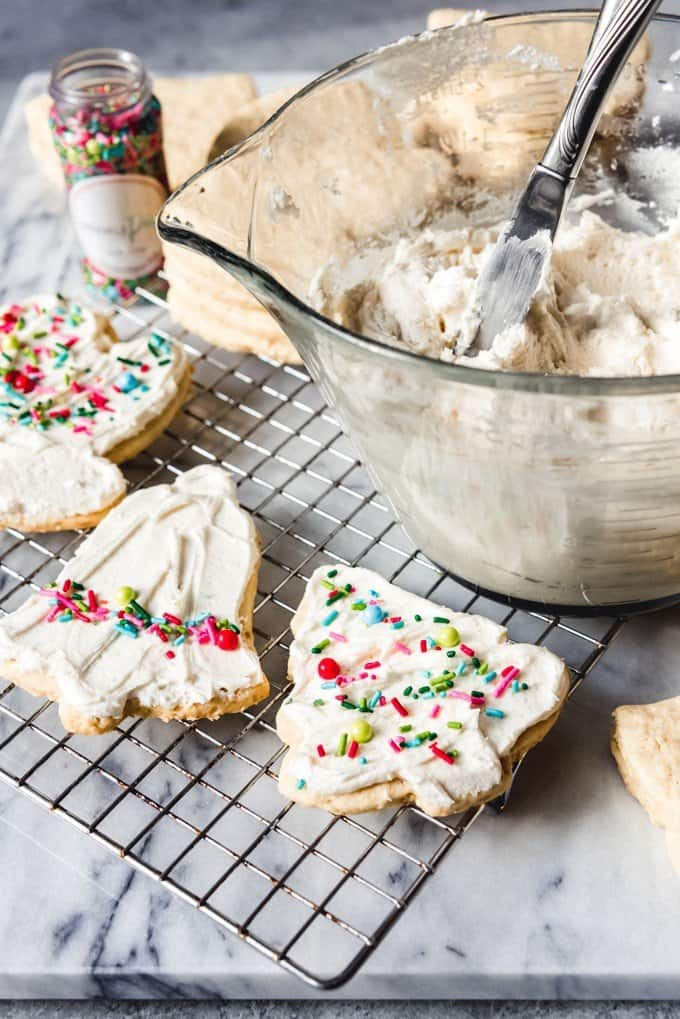 An image of a bowl of easy sugar cookie frosting with frosted oatmeal rolled sugar cookies in front of it.