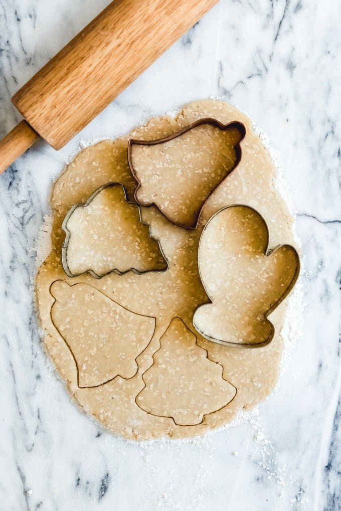 An image of oatmeal cut-out sugar cookie dough on a marble surface, rolled to 1/4-inch thickness and cut into the shapes of trees, bells, and mittens using cookie cutters.
