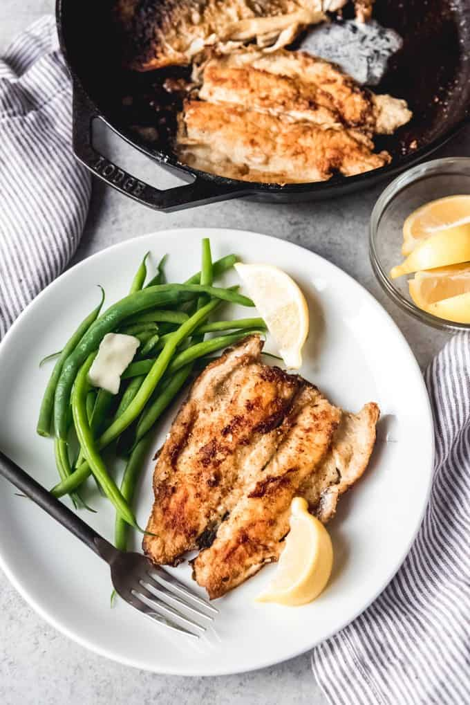 pan fried trout fillet on a plate with lemon wedges and green beans with more in a cast iron skillet to the side
