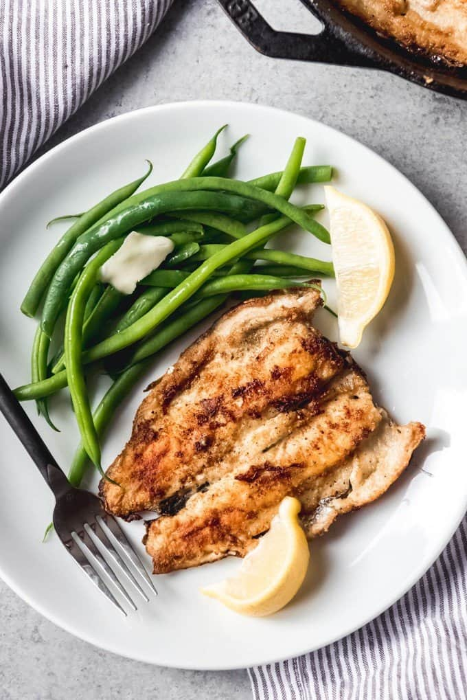 An image of a plate of pan fried rainbow trout served with lemon wedges and green beans.