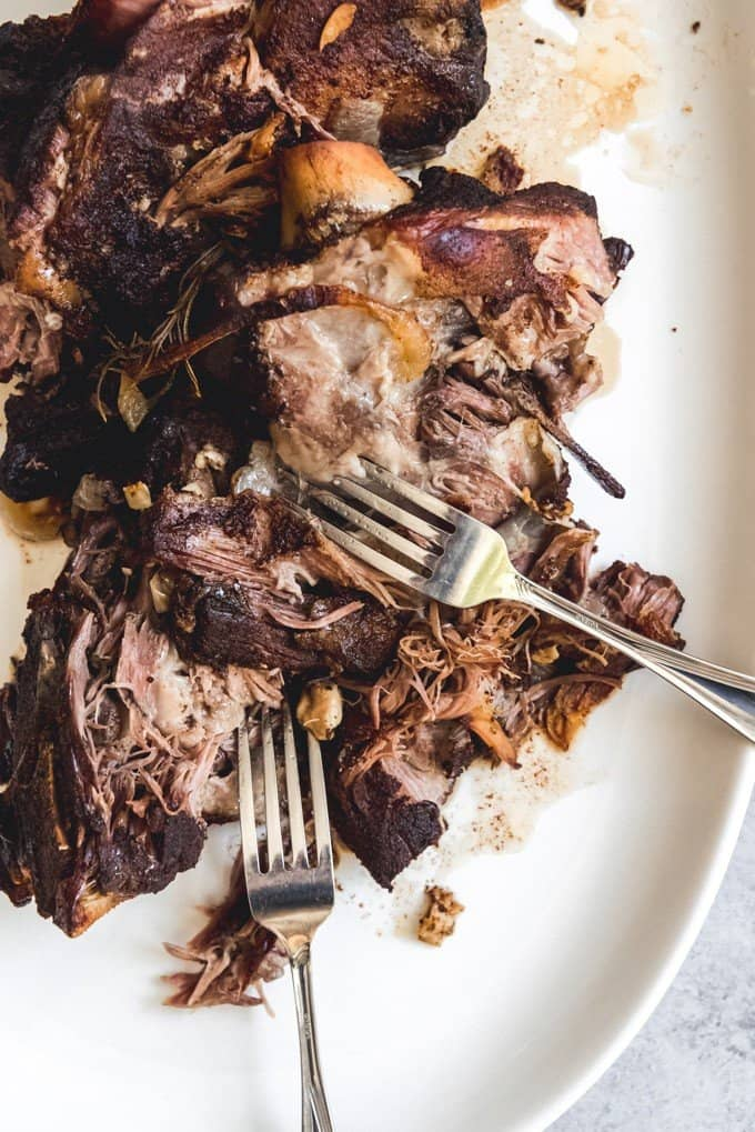An image of bone-in slow roasted lamb shoulder being pulled apart with two forks.