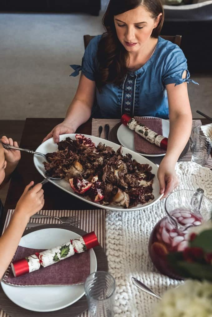 An image of a woman holding a platter of slow roasted lamb shoulder with pomegranate apricot glaze while someone else serves from it.