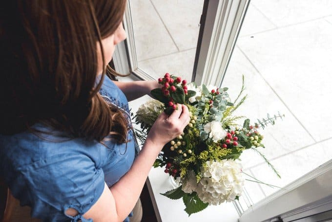 An image of a woman arranging flowers for a Christmas floral arrangement.