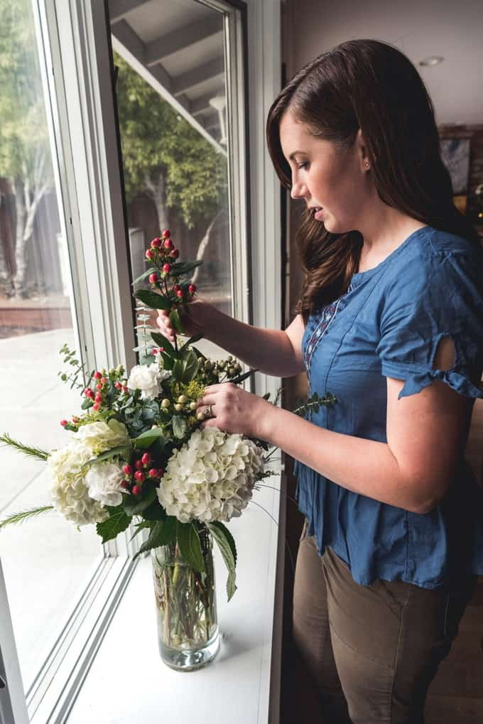 a woman adding pieces to her floral centerpiece at a window