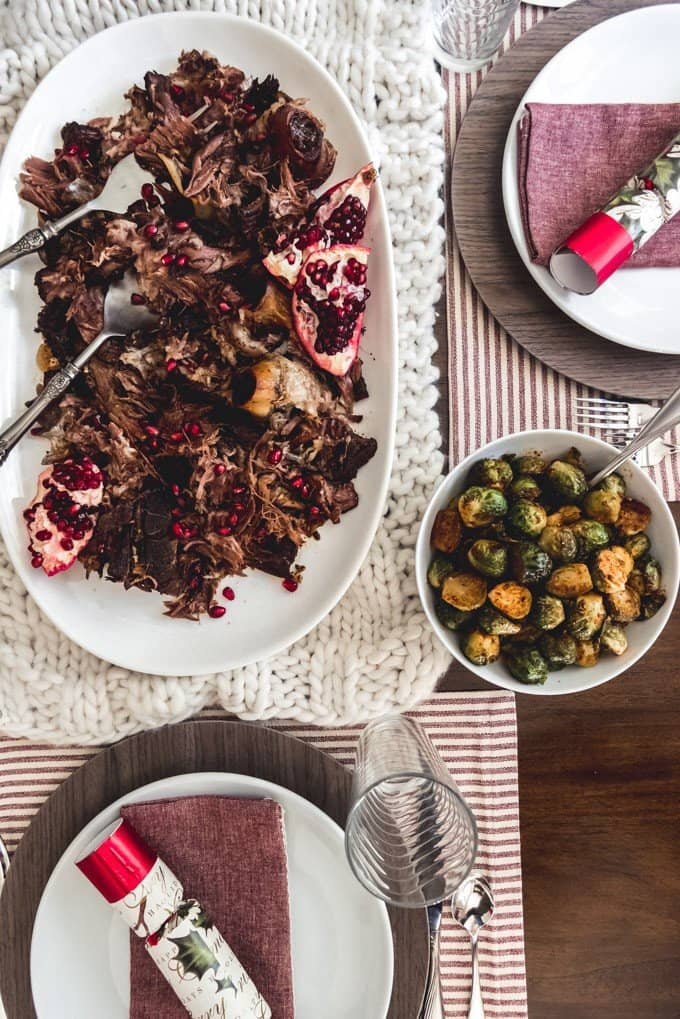 An image of a table set for dinner with a serving plate of slow roasted pomegranate lamb shoulder for the main course and pastrami spiced brussels sprouts on the side.