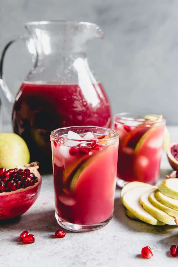 Pomegranate in a Pear Tree Punch in glasses and in a pitcher with fresh fruit scattered around