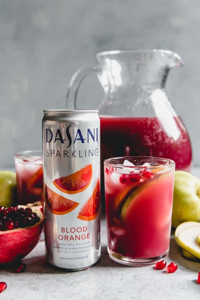 An image of a can of DASANI Sparkling Blood Orange flavored water beside a glass of Pomegranate in a Pear Tree Punch made with the flavors of blood oranges, pomegranate juice, and pear juice, then garnished with fruit.