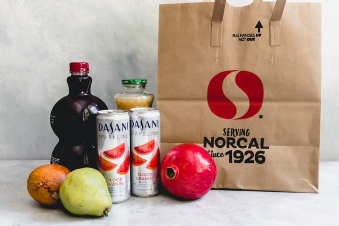 An image showing a Safeway shopping bag with pomegranate juice, pear juice, DASANI sparkling blood orange water, and some fruit.