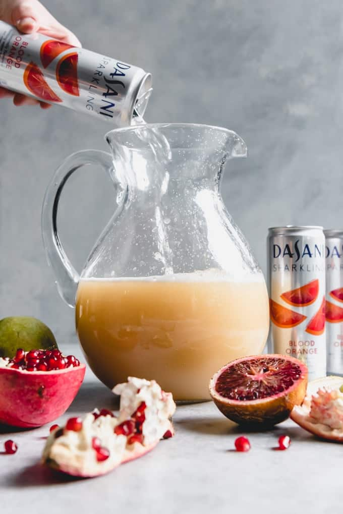 An image of a glass pitcher partly filled with pear juice and a hand pouring a can of DASANI Sparkling Blood Orange flavored water into the pitcher.