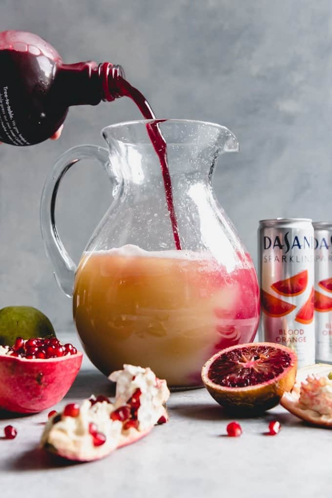 An image of pomegranate juice being poured into a tall glass pitcher along with pear juice and blood orange sparkling water to create a pomegranate in a pear tree punch for a festive holiday party.