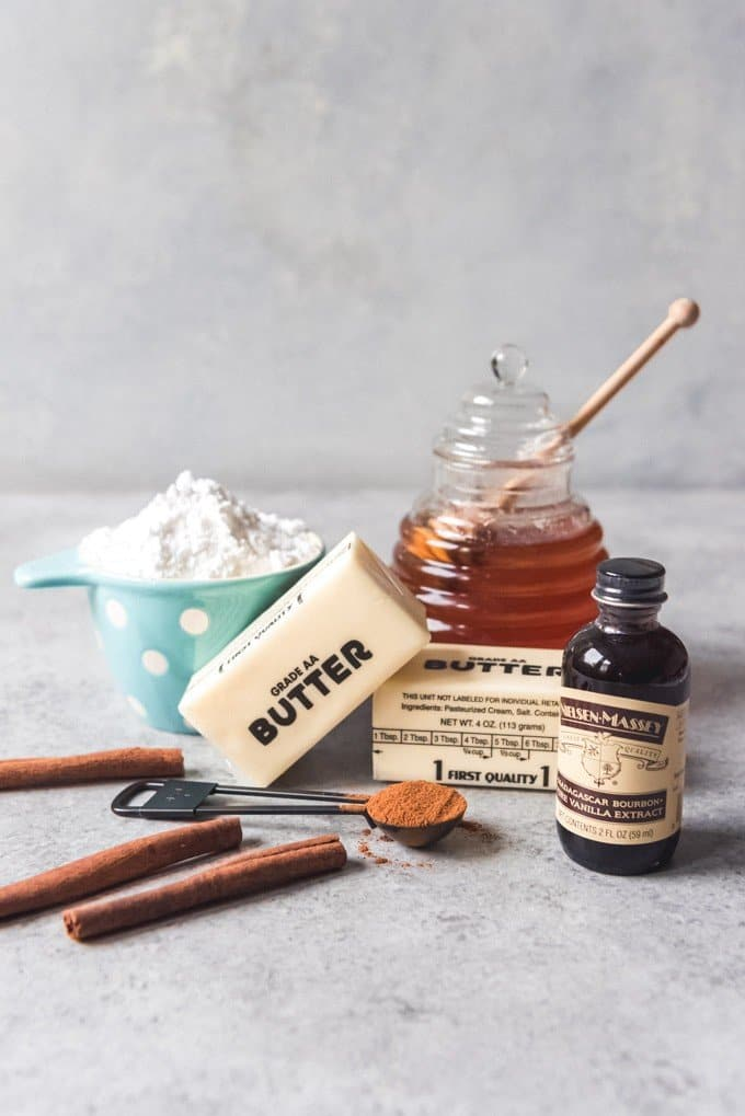 An image of the ingredients for making homemade cinnamon honey butter - butter, honey, powdered sugar, cinnamon, and vanilla.