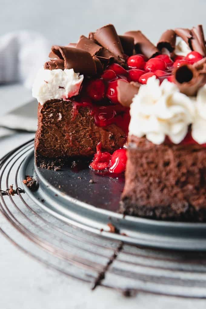An image of a sliced cherry chocolate cheesecake garnished with whipped cream and chocolate curls.