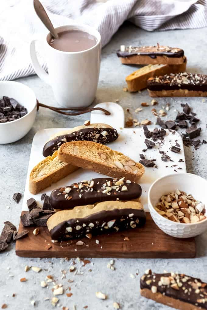 An image of classic Italian biscotti with toasted almonds and dark chocolate, piled on a cutting board.